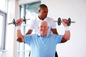elderly man doing physical therapy assisted by a caregiver