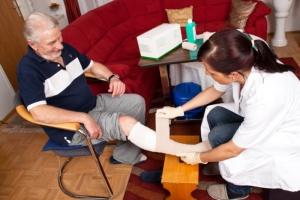 caregiver dressing an elderly man's wound